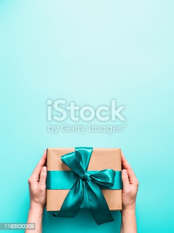 Female hands hold big gift box on turquoise blue background, copy space. Caucasian girl hands holding gift box in craft wrapping paper with green satin ribbon. Christmas, New Year or Birthday present