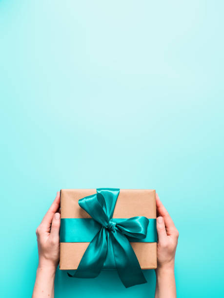 female hands hold gift box, copy space top - prenda imagens e fotografias de stock