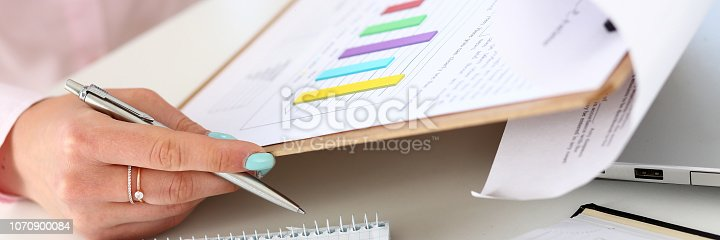 istock Female hands hold silver pen and pad 1070900084