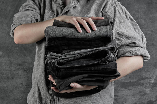 Female hands hold stack of neatly folded dark clothes isolated on black gray background close-up