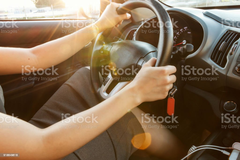 Female hands hold the steering wheel, close-up. A woman is driving a car. Selective focus. Toned. stock photo