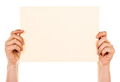 A woman's hands hold up an A4 sheet of  textured cream-coloured  paper against a white background, horizontal orientation.