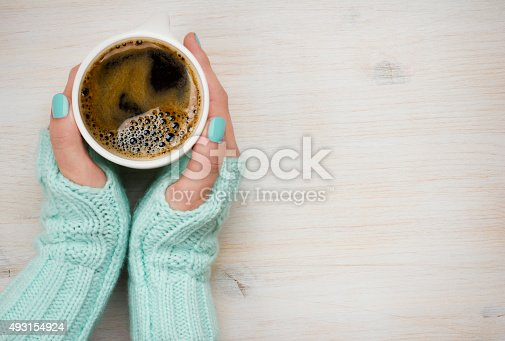 istock Female hands holding a coffee mug in knitted mittens 493154924