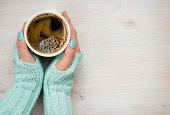 女性の手を持つコーヒーマグミトンのニット