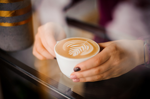 istock Female hands holding a cup of coffee latte with art outside the window 915783106