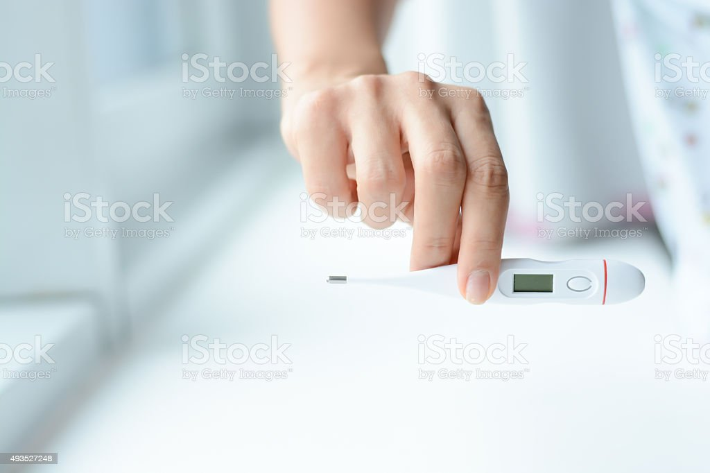 Female hands holding a digital thermometer stock photo
