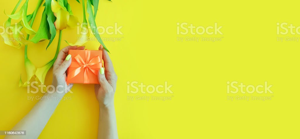 female hands holding a gift box flower on a colored background