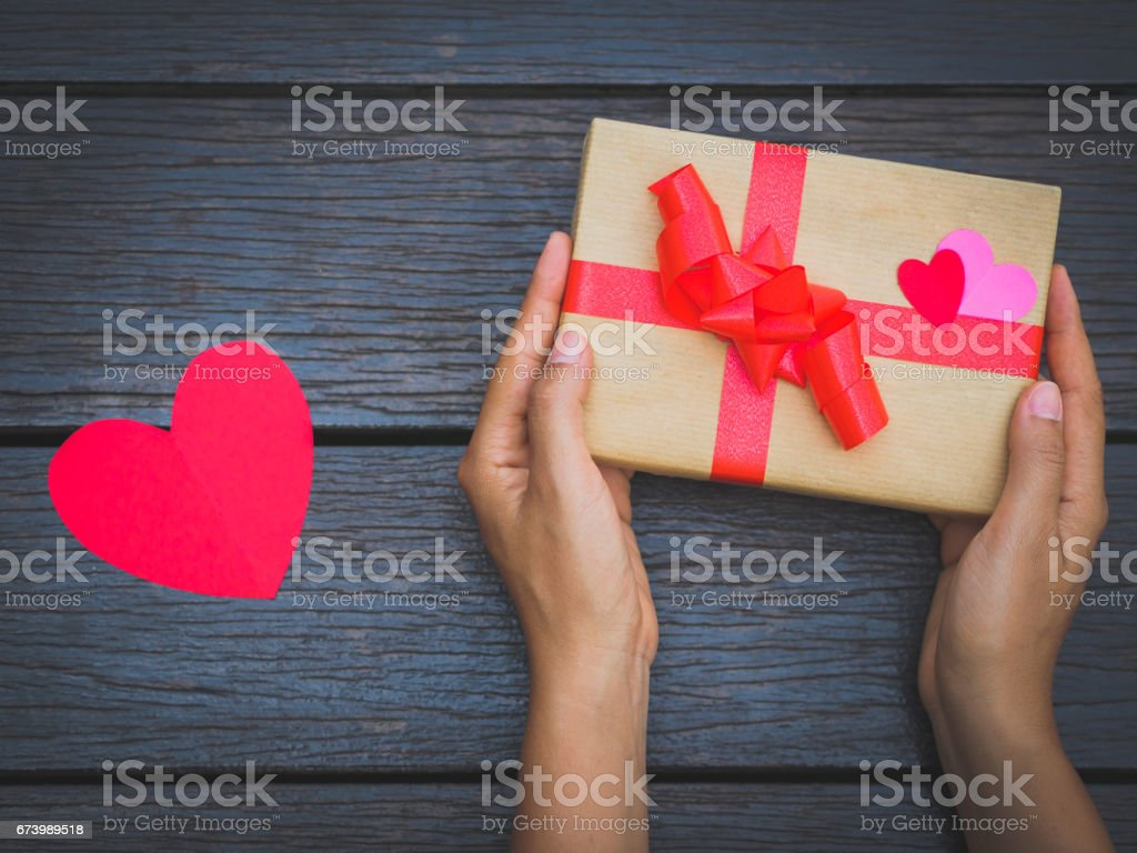 female hands holding a gift box on wooden table. Festive background for your design. royalty-free stock photo