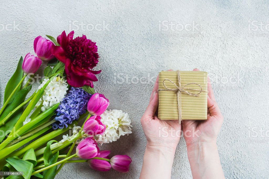 Female hands holding a gift or present box, flowers tulips, peony,...