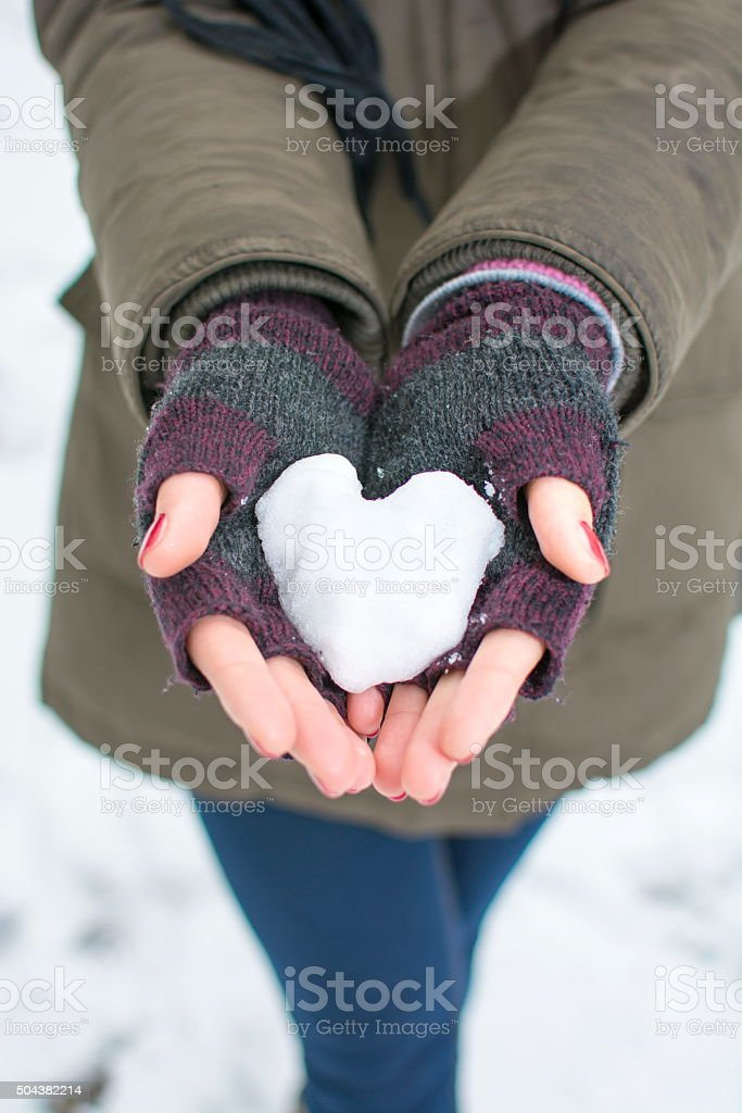 female hands holding a heart made out of snow stock photo