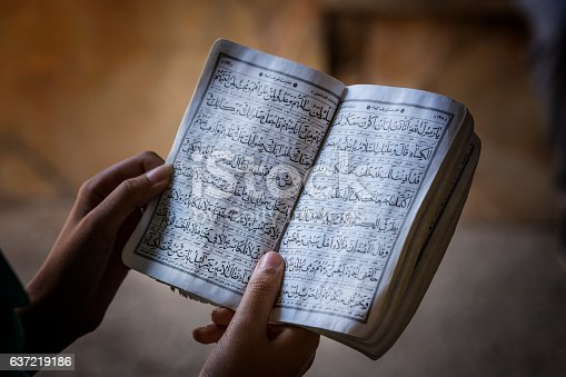 Hands of a woman who is reading a koran book in persian language, also called Farsi.