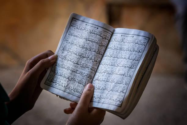 female hands holding a koran book - zeichen lesen stock-fotos und bilder