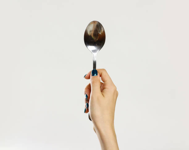 Female hands holding a metal tablespoon. Isolated on gray background. Closeup stock photo