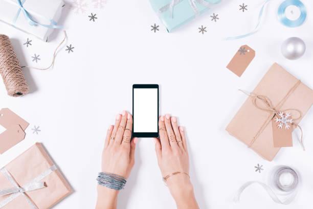 weibliche hände halten mobiltelefon - weihnachtsprogramm stock-fotos und bilder