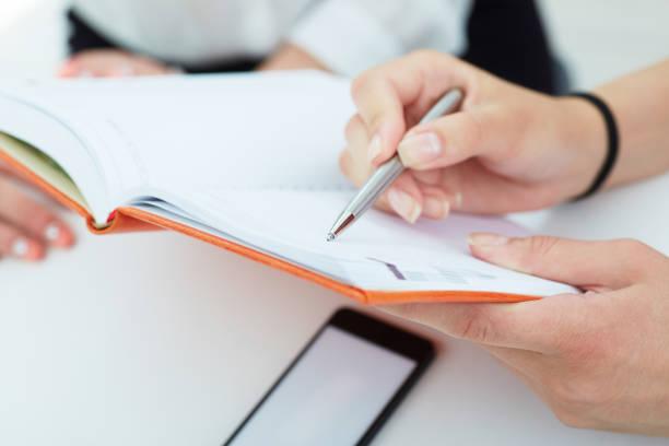 Weibliche Hände halten einen Silberstift Closeup. Business-Frau zeigt auf den Datensatz im Notebook. Business, Jobangebot, Wirtschaftsprüfer-Konzept. – Foto