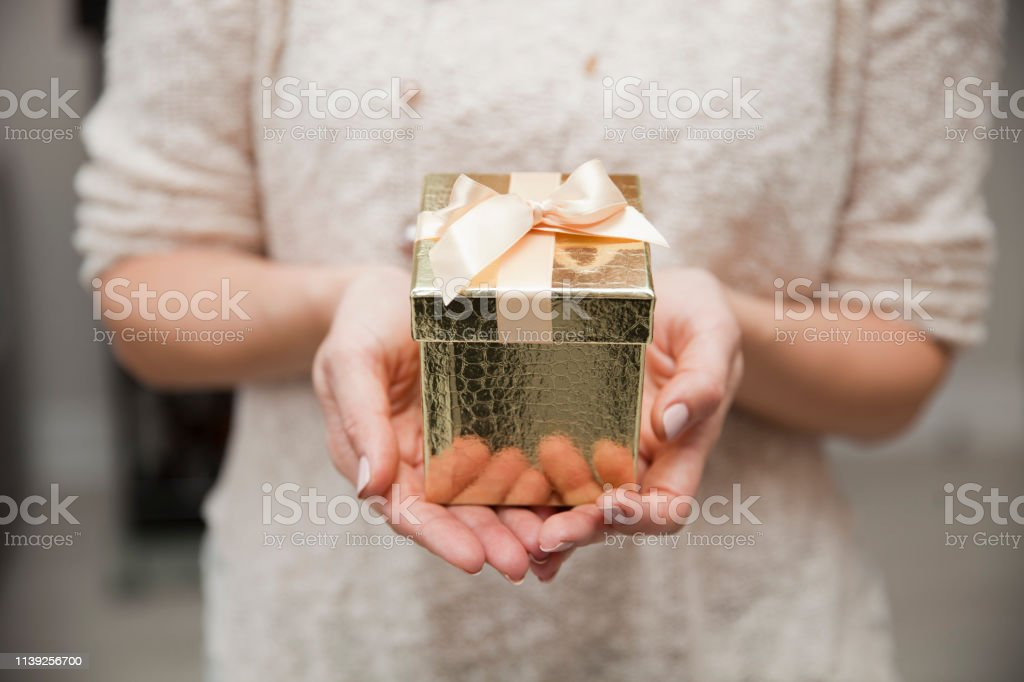 woman holding a gold present box