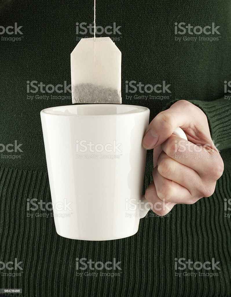 female hands holding a teacup and teabag royalty-free stock photo