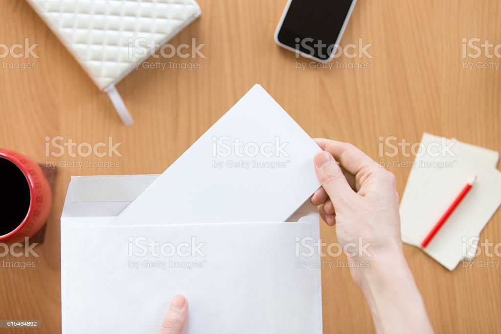 Female hands holding an envelope with a sheet over office stock photo