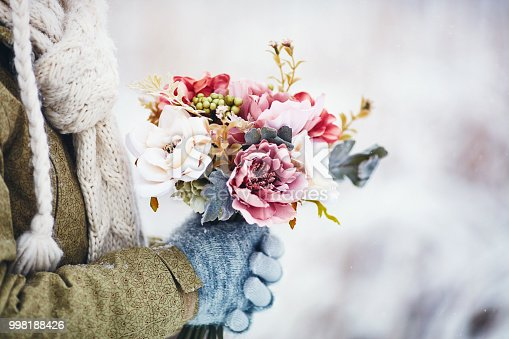 Female hands holding beautiful flower bouquet in snowy weather