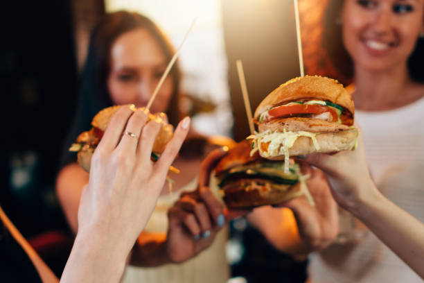 Female hands holding big tasty juicy hamburgers with blurred women in background stock photo