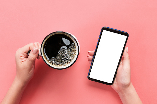istock Female hands holding black mobile phone with blank white screen and mug of coffee. Mockup image with copy space. Top view on pink background, flat lay 1070707440