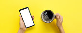 istock Female hands holding black mobile phone with blank white screen and mug of coffee. Mockup image with copy space for you design. Top view banner on yellow background, flat lay 1087559308