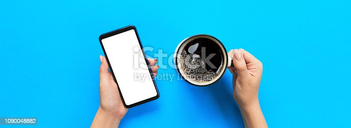 899410700istockphoto Female hands holding black mobile phone with blank white screen and mug of coffee. Mockup image with copy space for you design. Top view banner on blue background, flat lay 1090048882