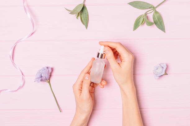 Female hands holding bottle of cosmetic serum stock photo