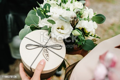Female hands holding bouquet of flowers and gift round box with lid, flat lay. Summer stylish composition. Woman give brown box. Happy Mother's Day, Women's Day, Valentine's Day or Birthday.