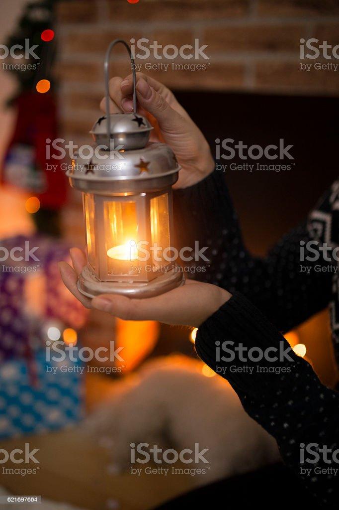 Female Hands Holding Christmas Lantern with Burning Candle stock photo