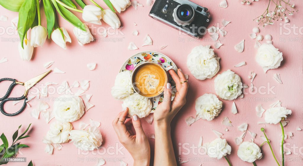 Flat-lay of female hands holding cup of coffee, scissors, film...
