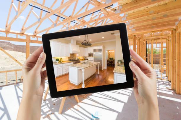 femmes mains tenant ordinateur tablette avec cuisine fini sur écran, construction charpente derrière. - travaux maison photos et images de collection