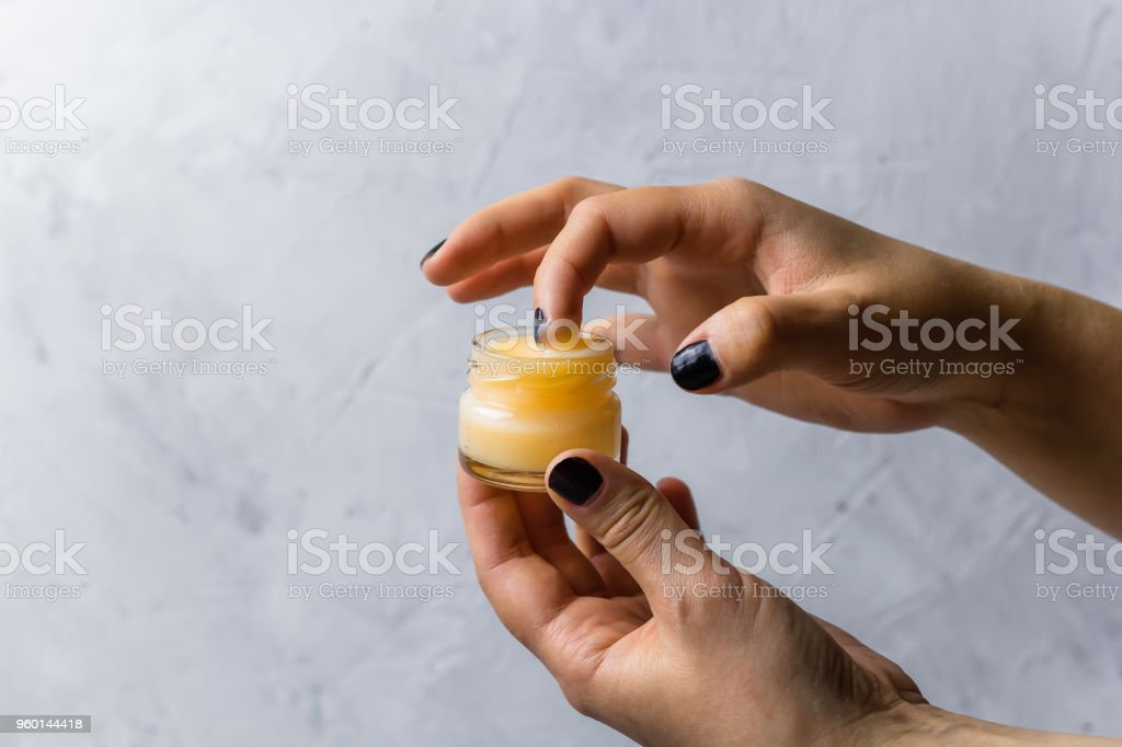 female hands holding cosmetic product stock photo