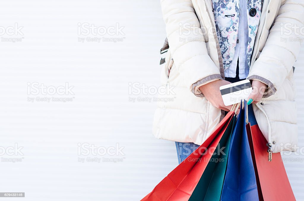 Female hands holding credit card and shopping bags stock photo