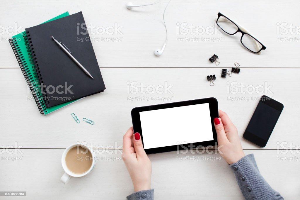Female hands holding digital tablet. Office desktop on white...