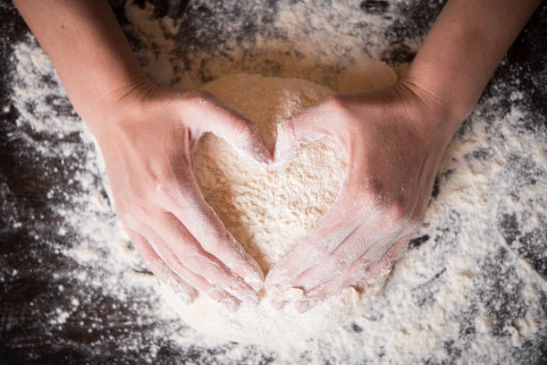 Female hands holding dough in heart shape Female hands holding dough in heart shape baking bread stock pictures, royalty-free photos & images