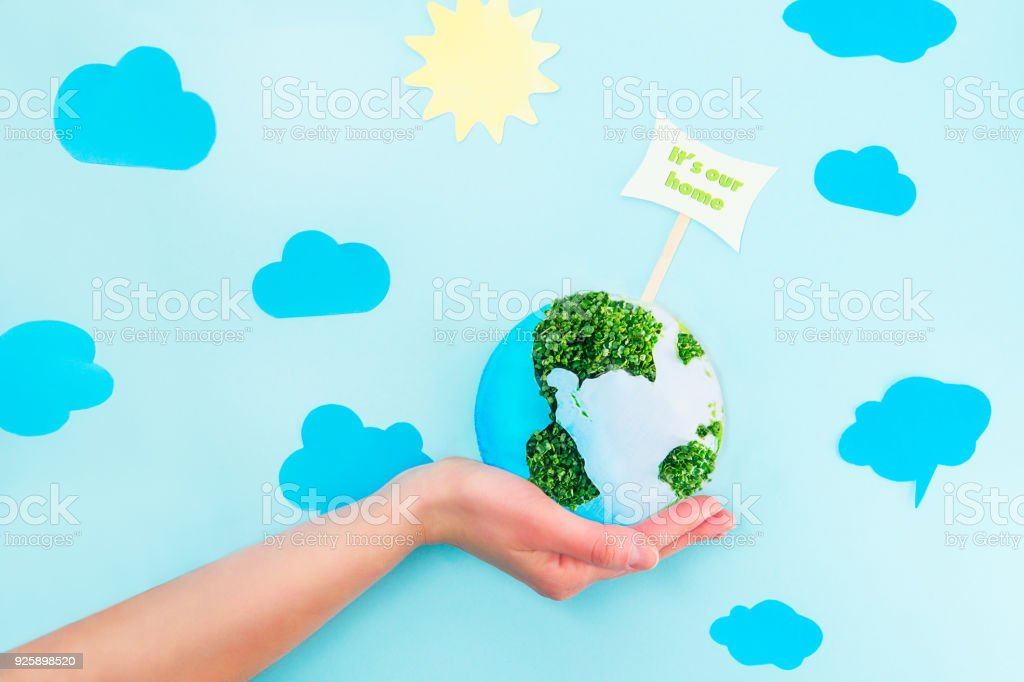 Female Hands holding Earth paper and green sprouts collage model with It's our home pointer on blue background with paper sun and clouds. Earth in your hands, Saving planet concept. stock photo