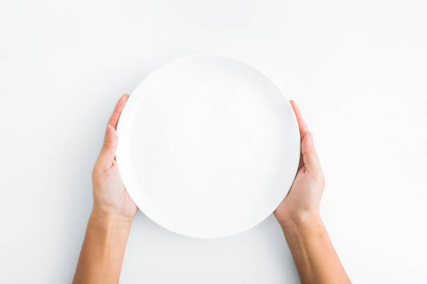 Female hands holding empty plate on white background stock photo