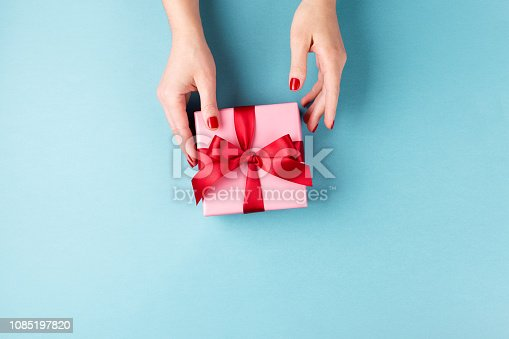 istock Female hands holding gift box on blue background. 1085197820