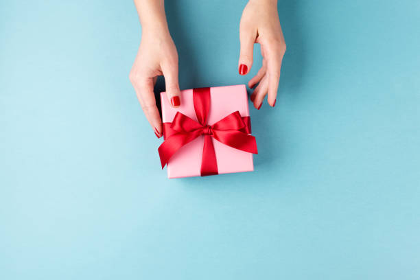 female hands holding gift box on blue background. - gift стоковые фото и изображения