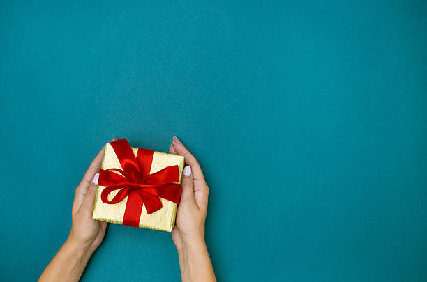 Female hands holding gift on blue background stock photo