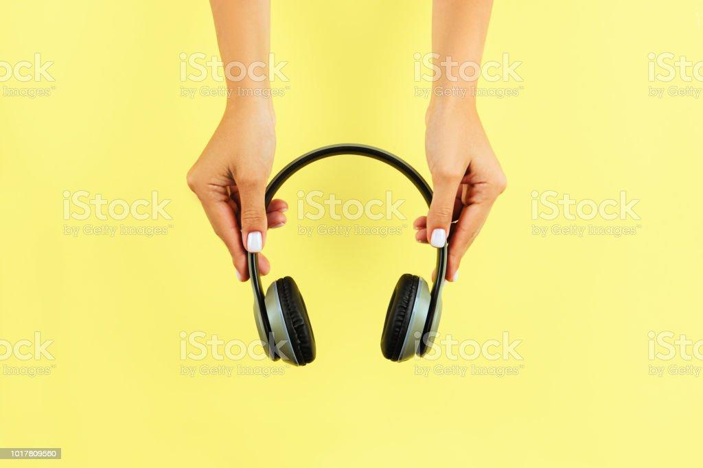 Female Hands Holding Headphones stock photo