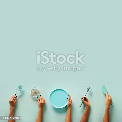 istock Female hands holding kitchen tools, sieve, rolling pin, plate, sieve, brush, whisk, spatula for baking and cooking over pastel blue background. Food frame, bake concept with copy space. 1147568959