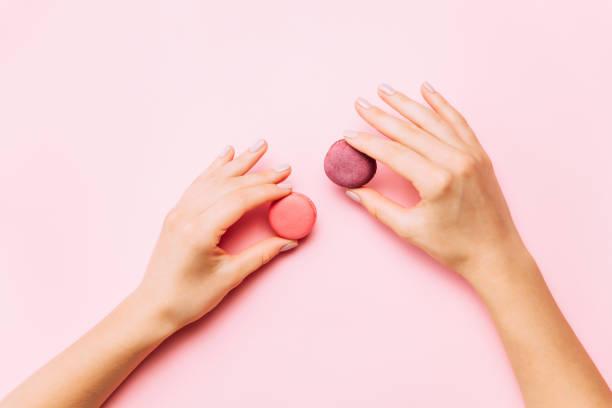 weibliche hände halten macarons auf rosa hintergrund. - bester nagellack stock-fotos und bilder