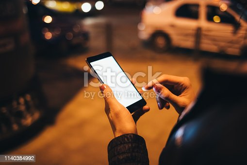istock Female hands holding mobile device with blank screen 1140384992