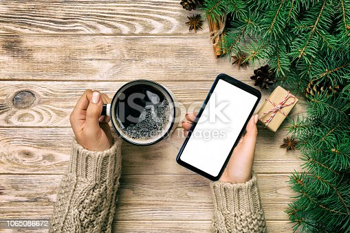 847905020 istock photo Female hands holding modern smartphone with mosk up and mug of coffee on wooden vintage table with christmas decoration. top view 1065086672