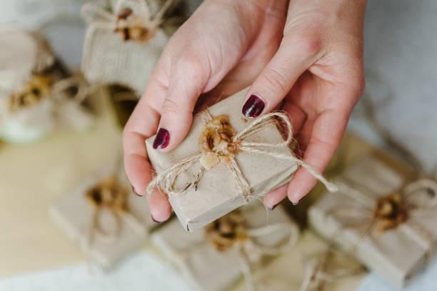 weibliche hände halten naturkosmetik der körperpflege in geschenkverpackung: seife. kosmetologie schönheit. hautpflege. der fokus liegt auf einer frauenhand. gesichtspflege. - basteln mit zeitungspapier stock-fotos und bilder