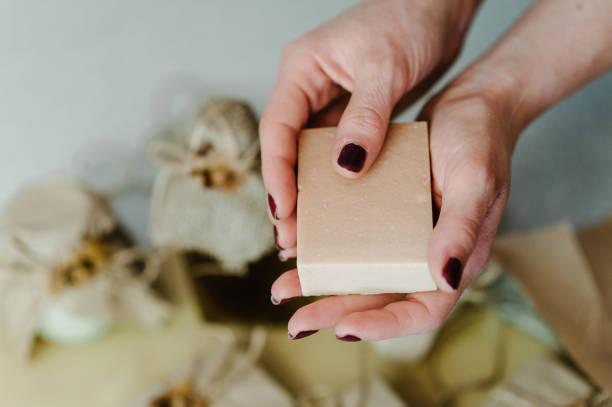 weibliche hände halten naturkosmetik der körperpflege: seife. kosmetologie schönheit. hautpflege. der fokus liegt auf einer frauenhand. gesichtspflege. platz für text und werbung. - basteln mit zeitungspapier stock-fotos und bilder