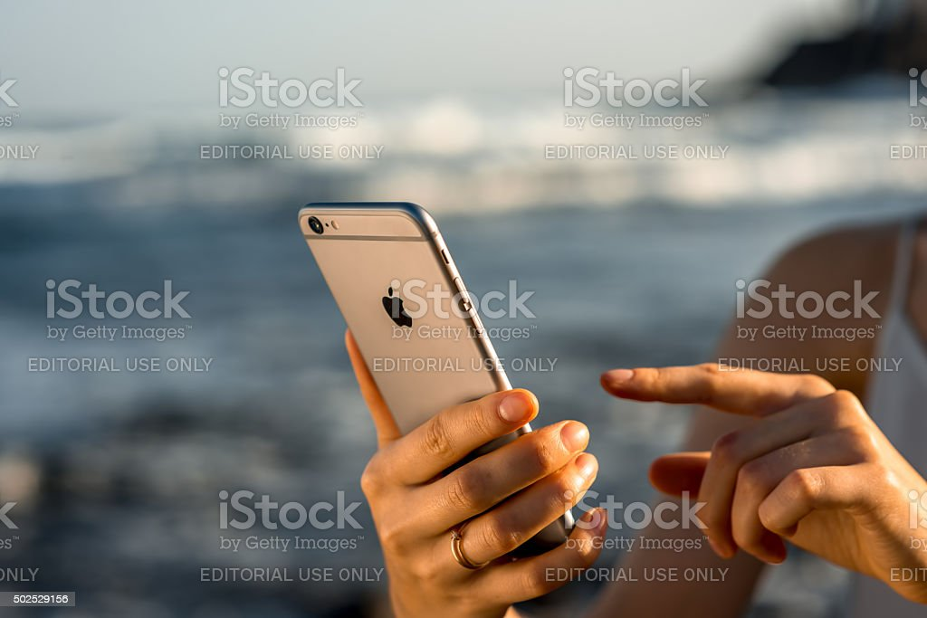 Female hands holding new iPhone 6s Space Gray stock photo
