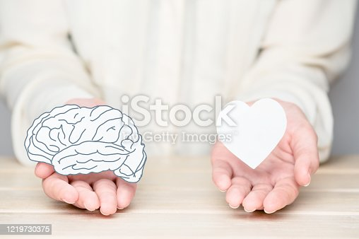 Female hands holding paper cut brain and soul. Conflict between emotions and rational thinking. Balance and equilibrium between mind and heart concept.